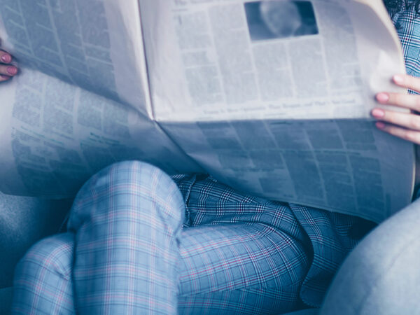 Im Sessel sitzende und Zeitung lesende Person